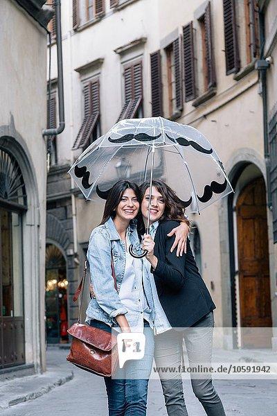 Lesbisches Paar  das zusammen in der Straße steht und den Regenschirm hält und lächelnd in die Kamera schaut  Florenz  Toskana  Italien