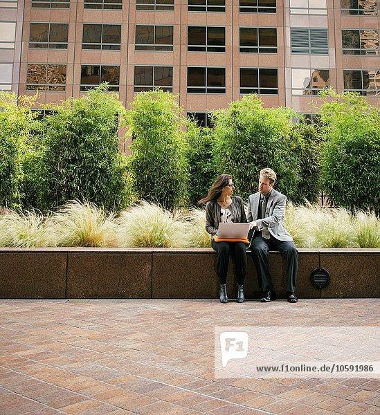 Geschäftsmann und Frau an der Wand sitzend mit Laptop