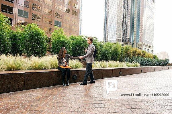 Geschäftsmann und Frau beim Händeschütteln vor dem Bürogebäude