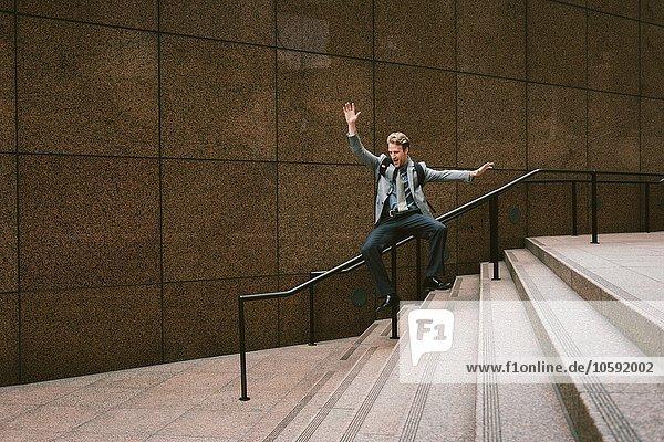 Geschäftsmann rutscht die Stadttreppe hinunter