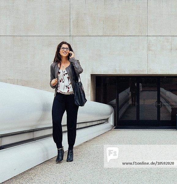 Geschäftsfrau im Gespräch auf dem Smartphone auf dem Gehweg