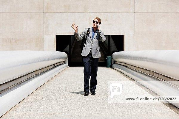 Geschäftsmann im Gespräch auf dem Smartphone auf dem Gehweg