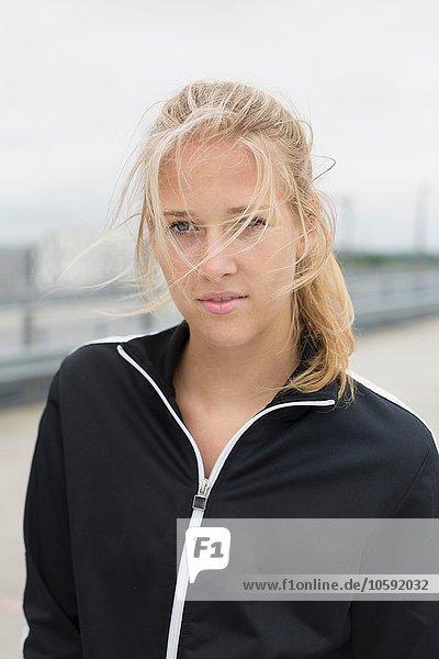 Porträt einer jungen Frau  in Sportbekleidung  im Freien