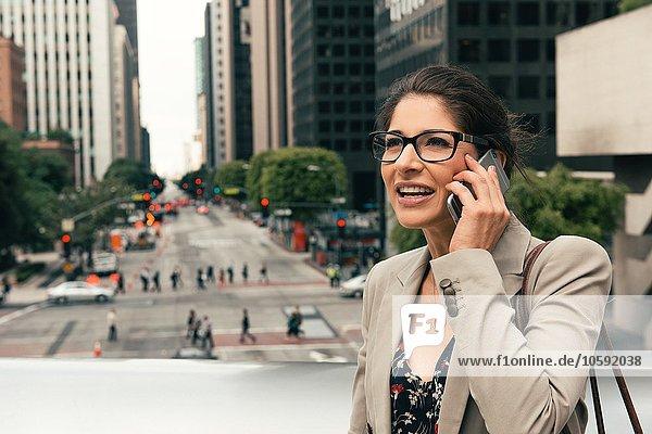 Geschäftsfrau im Gespräch auf dem Smartphone von der Fußgängerbrücke  Los Angeles  USA