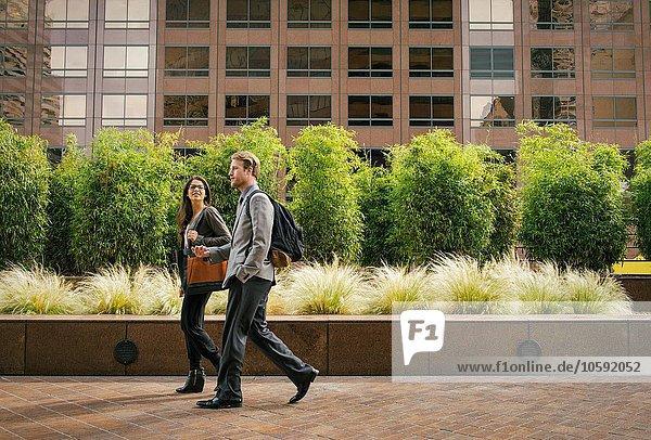 Geschäftsmann und -frau beim Gehen und Reden vor Bürogebäuden