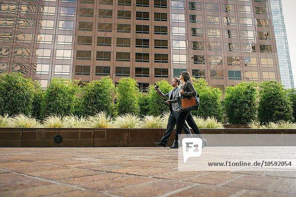 Geschäftsmann und Frau  die vor Bürogebäuden spazieren gehen