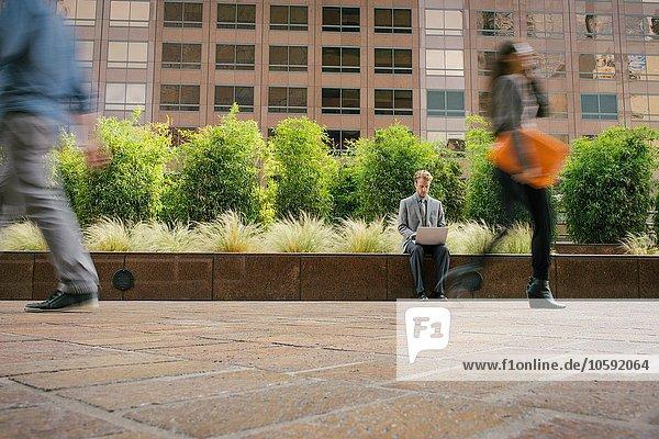 Geschäftsmann sitzend an der Wand vor dem Büro mit Laptop