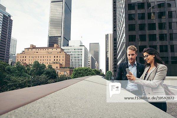 Geschäftsmann und Frau teilen sich Smartphone-Texte  Los Angeles  USA