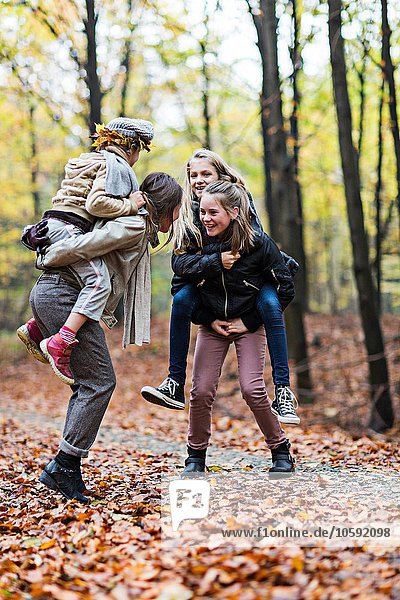Mother and daughters playing piggyback ride in autumn forest