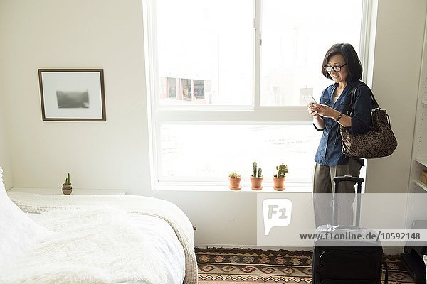 Mature woman standing in hotel room with suitcase using smartphone