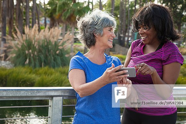 Mature female friends in park  looking at smartphone  laughing