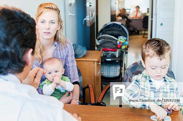 Mutter sitzend mit zwei Kindern  im Gespräch mit dem Arzt