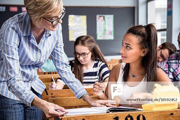 Lehrerin hilft Schülerin im Klassenzimmer