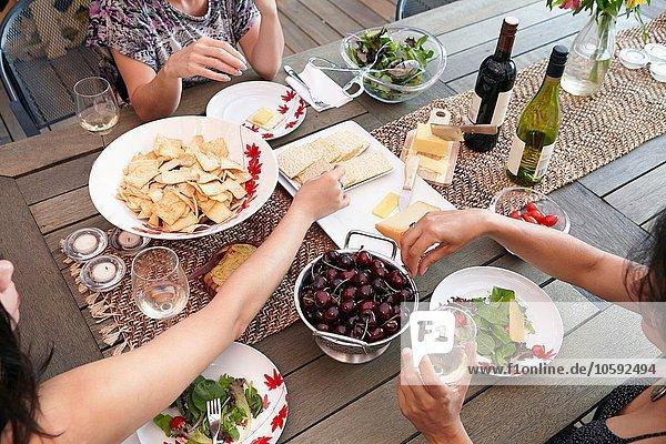 Beschnittene Ansicht der weiblichen Freunde beim Mittagessen auf der Terrasse