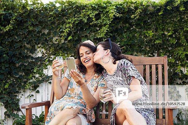 Zwei Frauen posieren für Smartphone Selfie auf der Terrasse