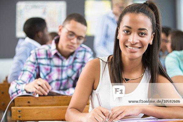 Porträt einer Schülerin  die am Schreibtisch im Klassenzimmer sitzt