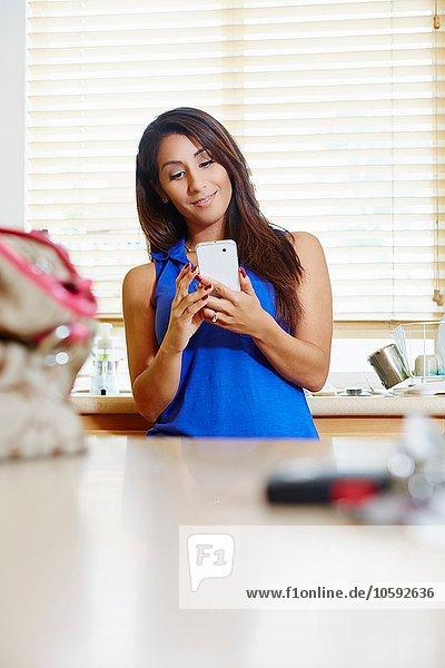 Frau mit Smartphone in der Küche