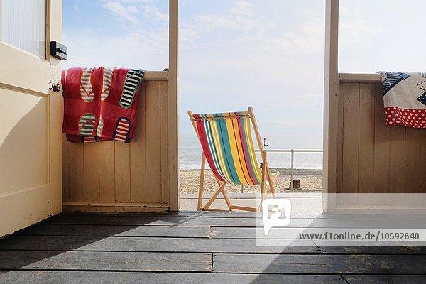 Leerer Liegestuhl vor der Strandhütte  Rückansicht