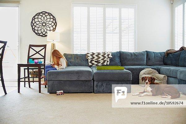 Mädchen mit digitalem Tablett auf Sofa im Wohnzimmer  Hund hinter ihr