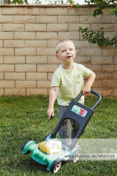 Junge spielt mit Spielzeugrasenmäher im Garten