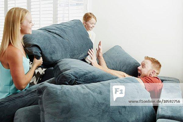 Familie spielt auf Kissenstapel im Wohnzimmer