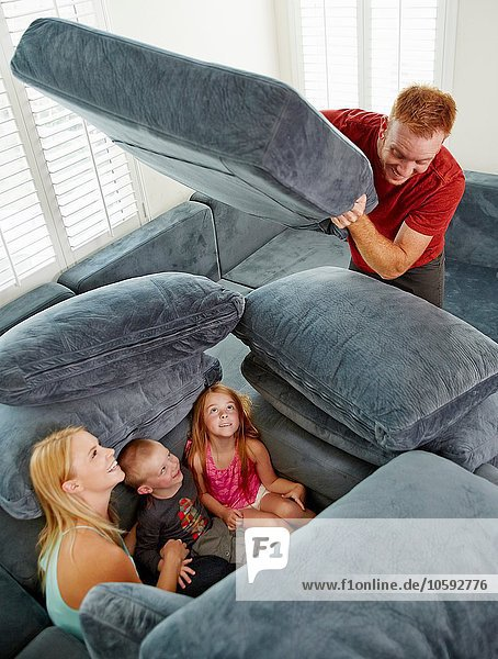 Vater  der die Familie bedeckt  sitzt zwischen den Kissen im Wohnzimmer.
