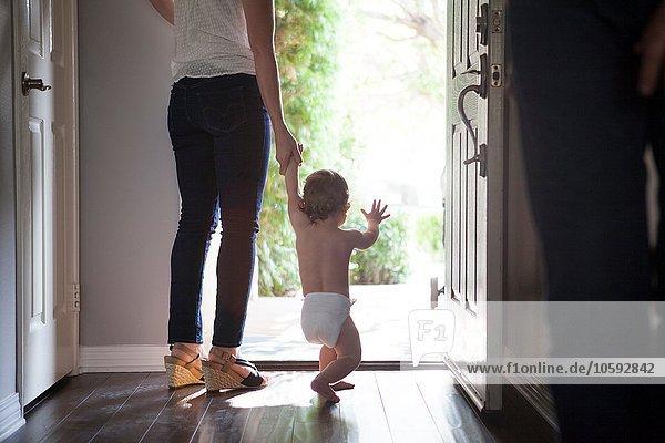 Rückansicht der Mutter mit den Händen der Jungen  die an der offenen Vordertür stehen.