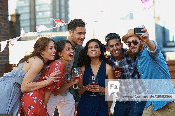 Freunde  die Selfie auf der Party am frühen Abend nehmen