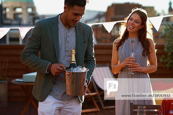 Mittleres erwachsenes Pärchen auf der Dachterrasse mit Eiskübel und Champagnerlächeln