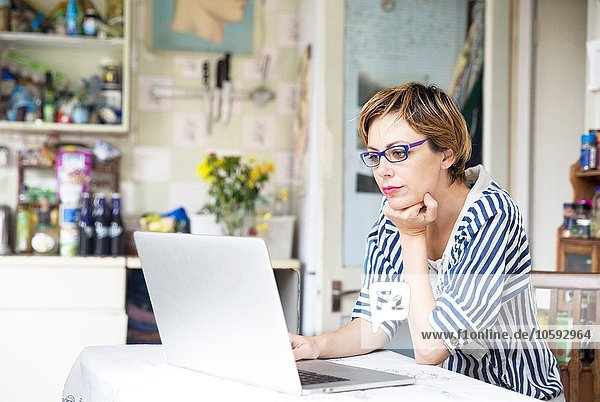 Mid adult woman working on laptop at kitchen table