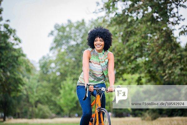 Vorderansicht einer reifen Frau mit einem Afro-Fahrrad  die lächelnd davonschaut.