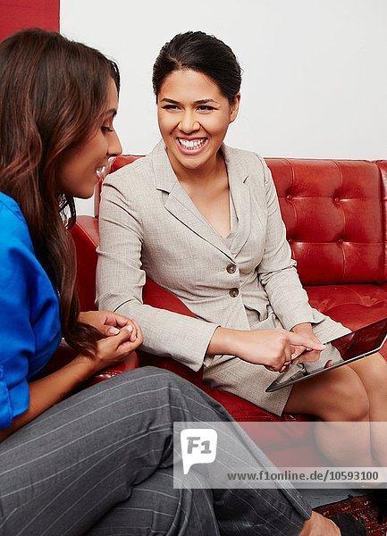 Zwei Geschäftsfrauen  die sich treffen und sich das digitale Tablett ansehen.