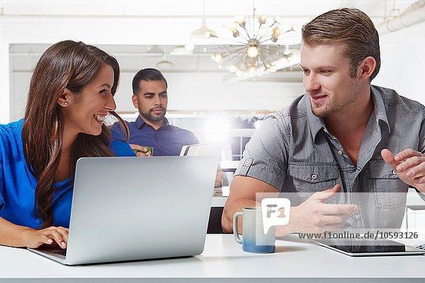Zwei Geschäftskollegen im Gespräch am Schreibtisch