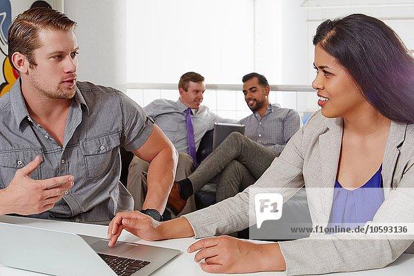 Geschäftsfrau und Geschäftsmann am Schreibtisch sitzen  diskutieren  Laptop benutzen