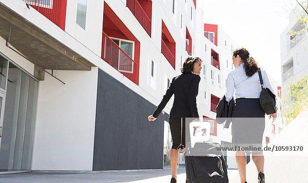 Zwei Geschäftsfrauen gehen die Straße entlang  ziehen Koffer  Rückansicht