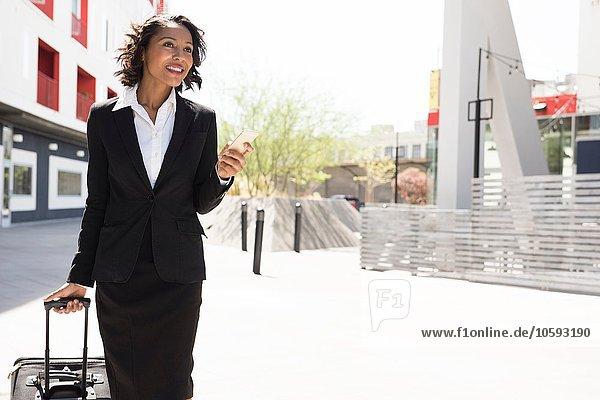 Junge Geschäftsfrau  Koffer ziehen  draußen