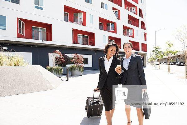 Zwei Geschäftsfrauen  die im Freien spazieren gehen und den Koffer ziehen.