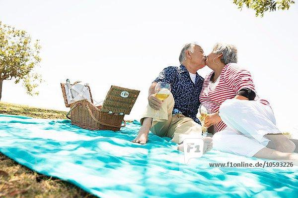 Seniorenpaar auf Picknickdecke sitzend  küssend