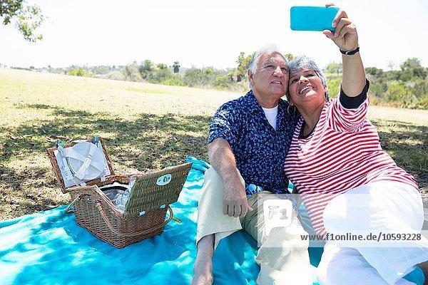 Seniorenpaar auf Picknickdecke sitzend  Selbstporträt mit Smartphone aufnehmend