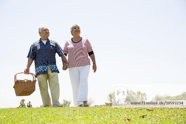 Seniorenpaar geht Hand in Hand mit Picknickkorb