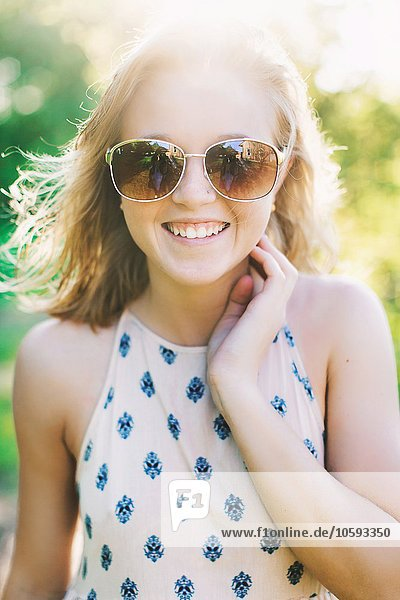 Porträt einer jungen Frau mit einer Sonnenbrille  die lächelnd auf die Kamera blickt.