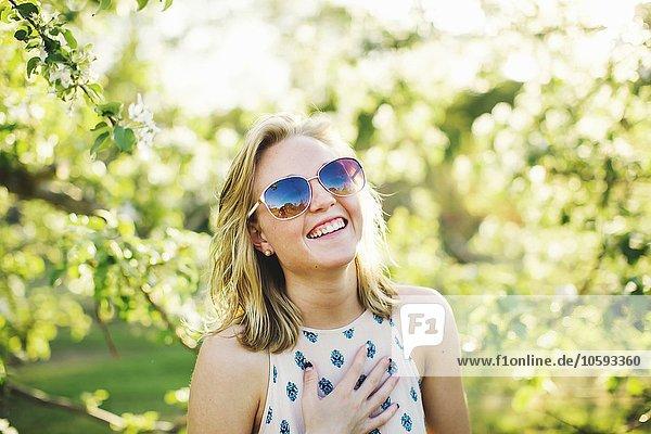 Kopf und Schultern einer jungen Frau mit Sonnenbrille  Hand auf der Brust mit Blick auf die Kamera lachend