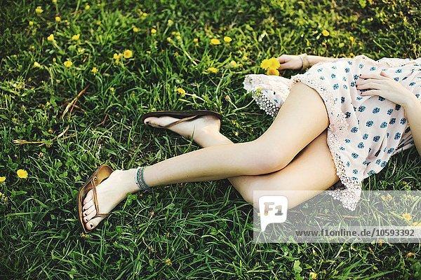 Taille unten Hochwinkelansicht der jungen Frau  die auf Gras liegt und Kleid  Flipflops und Knöchelarmband trägt.