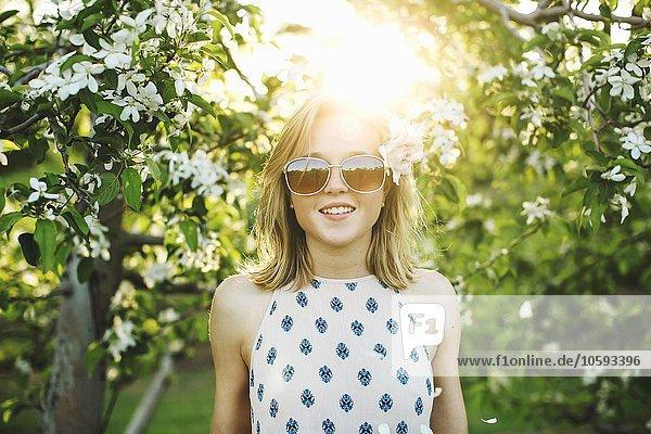 Junge Frau im Obstgarten  Blume im Haar  trägt eine Sonnenbrille und sieht lächelnd in die Kamera.