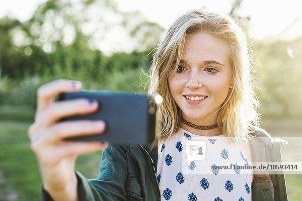Kopf und Schultern der jungen Frau mit Smartphone zu nehmen Selfie lächeln