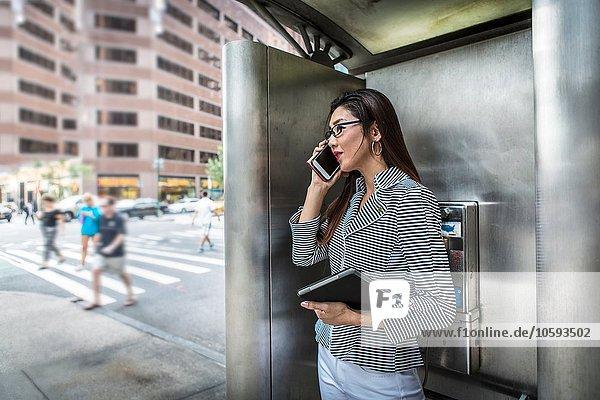 Geschäftsfrau mit Smartphone auf der Straße