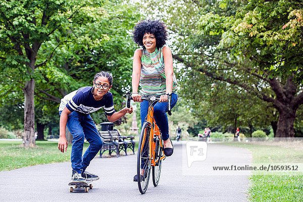 Skateboarding boy holding onto mothers bicycle in park
