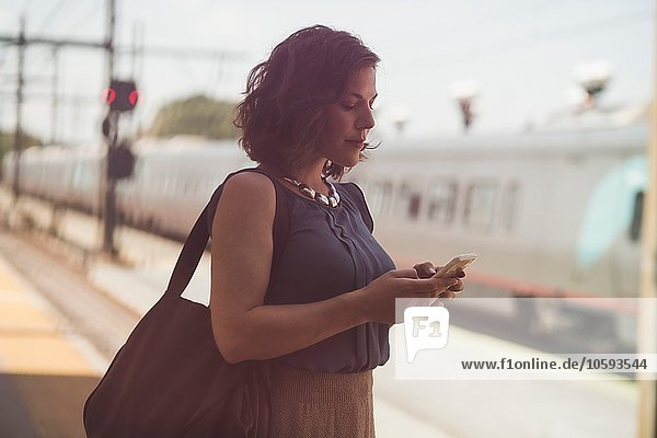 Mid adult woman waiting at train station  holding smartphone