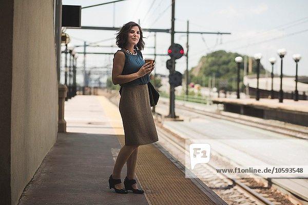 Mittlere erwachsene Frau wartet am Bahnhof und hält eine Kaffeetasse.