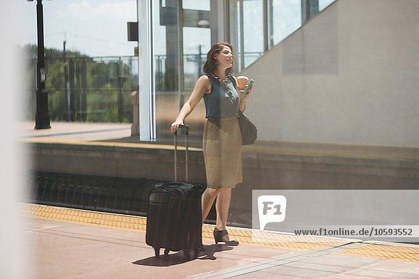 Mittlere erwachsene Frau wartet am Bahnhof  hält Koffer und Kaffeetasse in der Hand